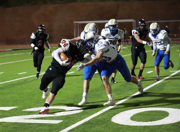 Coconino football player collides with two defenders.