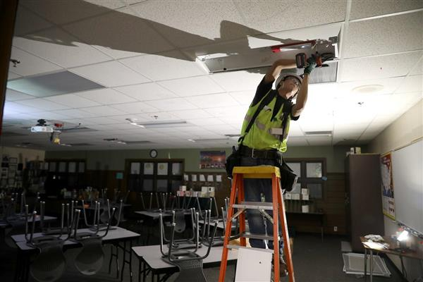 Greg Yazzie from Urban Energy Solutions installs a new light in classroom at Flagstaff High School.