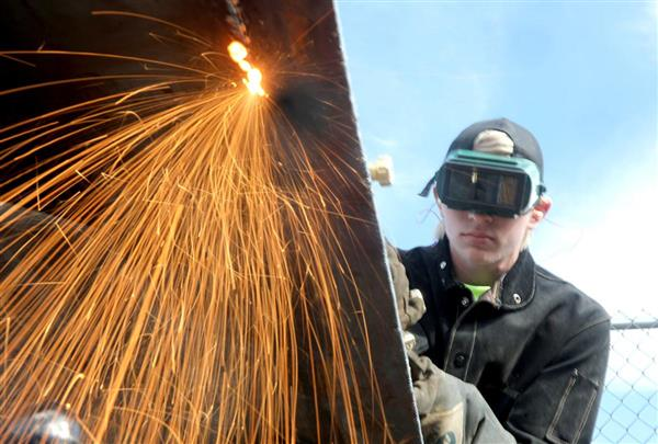 Kody Kelly uses an oxy-acetylene torch to cut sheet steel.