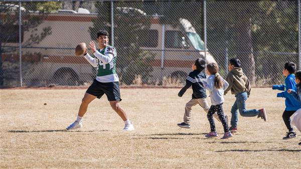 Flagstaff Eagles player throws football while younger students defend him.