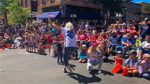 Assistant Superintendent Mary Kay Walton high fives children in the crowd at the 4th of July parade.