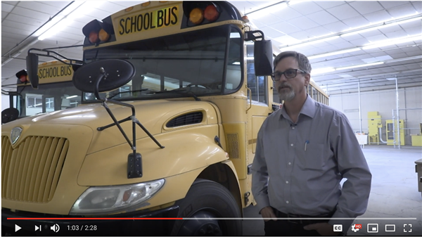 Transportation Director Patrick Fleming stands in front of a bus during an interview.