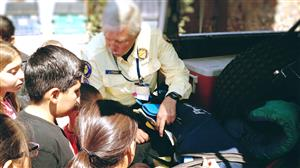 Search and Rescue gentleman showing students equipment in one of the vehicles