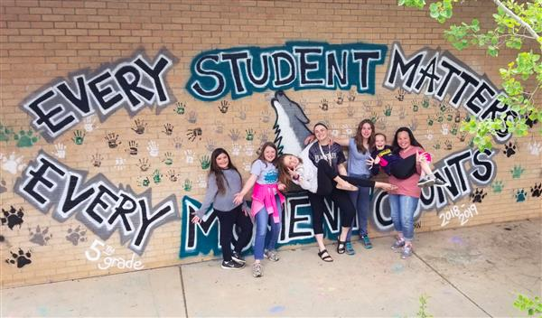 Ms. Clasen and students in front of the mural created by the 2019-2020 5th graders