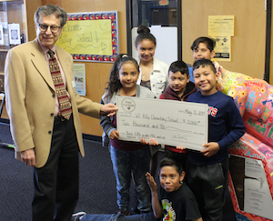 A member of the Forest Highlands Foundation with a large check presenting it to students