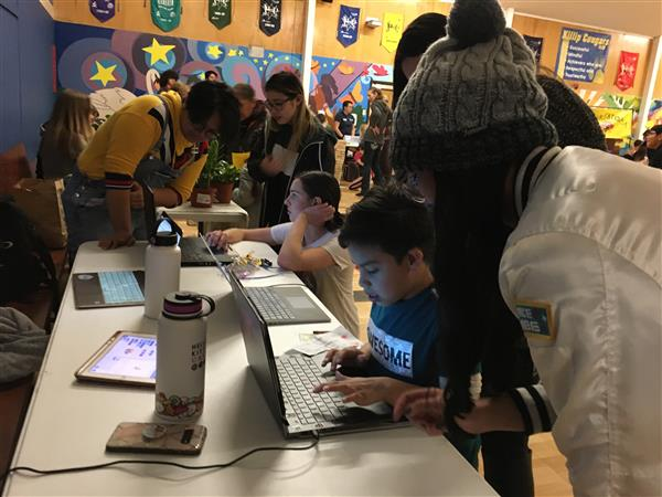 Members of the NAU Women Who Compute club assist students using laptops at the STEM Night event