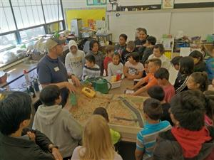 Students are gathered around a model of a forest and road to learn about fires.