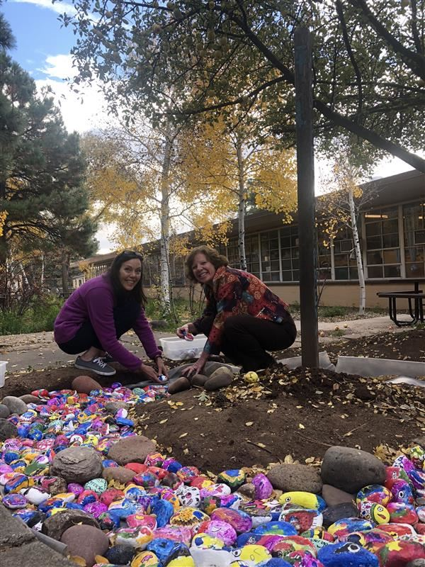 Teachers pose with rock art installation