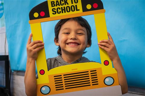 Student holds up a bus photo that says back to school.